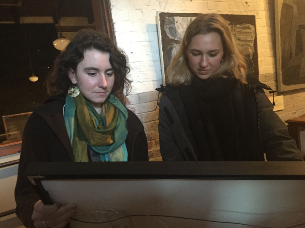 Colby Student Curators Nora Hill, left,  and Francesca Soriano selecting work for the exhibition.