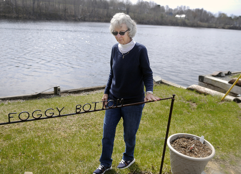 Sandra Alexander walks by the dock at Foggy Bottom Marine in Farmingdale on Sunday. She plans to continue operating the business on the Kennebec River several months after the death of her husband, Dan Alexander.