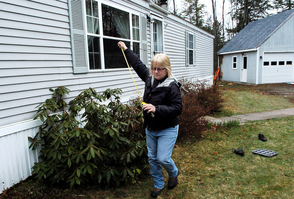 Sheryl Clifford, of Vision Government Solutions, measures a home Monday in Skowhegan for the one-year revaluation of residential and commercial properties in town.