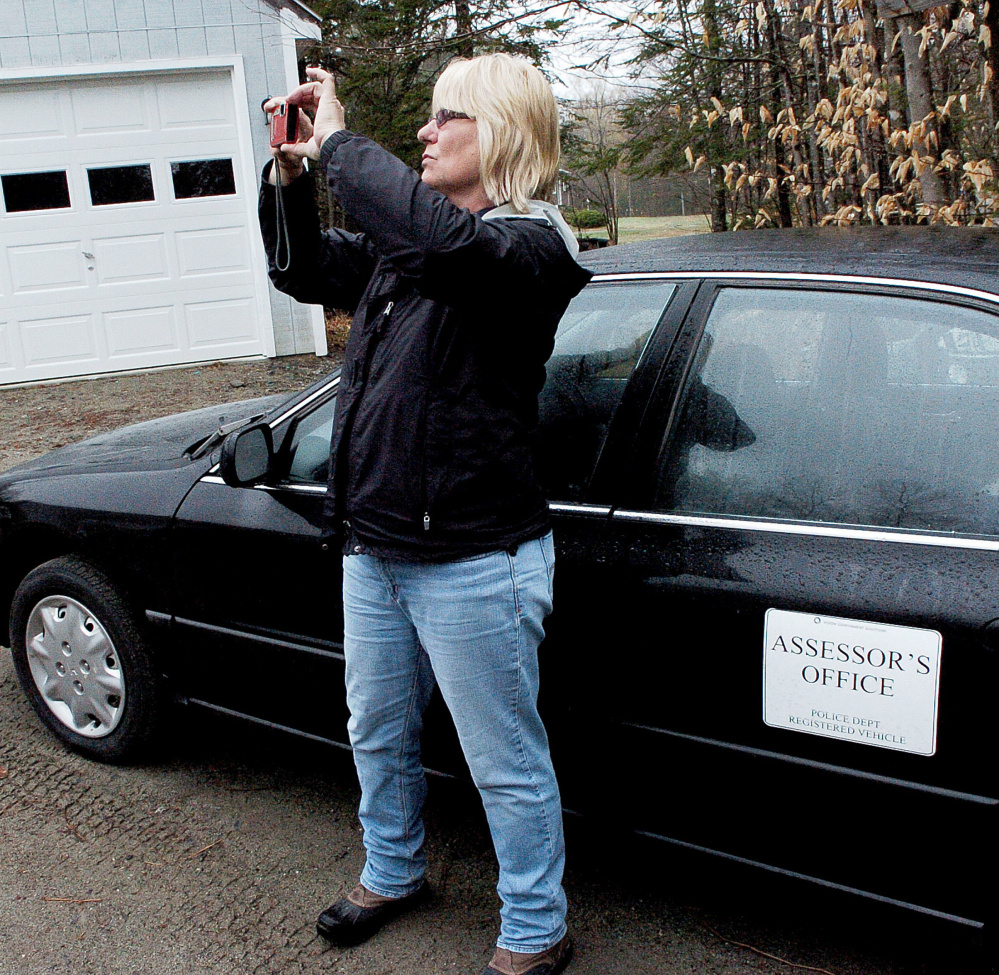 Sheryl Clifford, of Vision Government Solutions, photographs the exterior of buildings Monday at a residence in Skowhegan. The town is undergoing a revaluation of all residential and commercial properties.