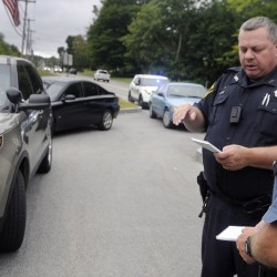 Gardiner police Officer Eric Testerman, left, shares information Sept. 13, 2015 with Maine State Police Trooper Randy Hall on the Kennebec River Rail Trail in Farmingdale after a report of an assault there.