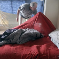 Staff photo by Andy Molloy Al Sugden searches his bedding for bedbugs Tuesday in his unit at 382 Water St. in Augusta.
