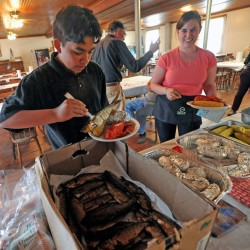 Fernando Cuares and Darcy Dow help themselves to smoked alewives and lobster in 2015 at the annual alewife festival dinner at the Benton Grange. This year's two-day Benton Alewife Festival is scheduled for May 13 and 14.