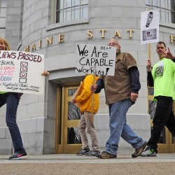 People hold signs Wednesday as they walk across the plaza between the Cross State Office Building and the State House during a rally for rights for the deaf and hard of hearing in Augusta.