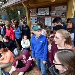Students from Warsaw Middle School stand in front of a trail kiosk Wednesday at the trailhead of the town farm property trail during the unveiling and dedication in Pittsfield.
