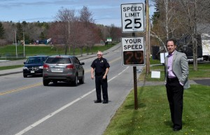 Waterville police Chief Joseph Massey, back left, and Alfond Youth Center CEO Ken Walsh, right, stand with a newly installed radar speed sign Friday across the street from the Youth Center on North Street in Waterville.