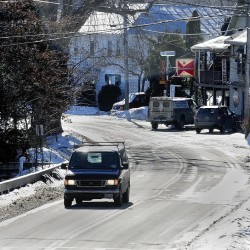 A van crosses a bridge over Mill Stream as it heads north out of Belgrade Lakes village on Route 27 in this Jan. 2014 file photo.