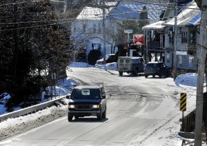 A van crosses a bridge over Mill Stream in January 2014 as it heads north out of Belgrade Lakes Village on Route 27.