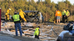 Police and firefighters work on March 18 at the scene of multi-vehicle accident on Route 17 near the Fitch Road intersection in Washington. A truck driver has been arrested in Virginia and charged in connection with the crash, which killed two people.