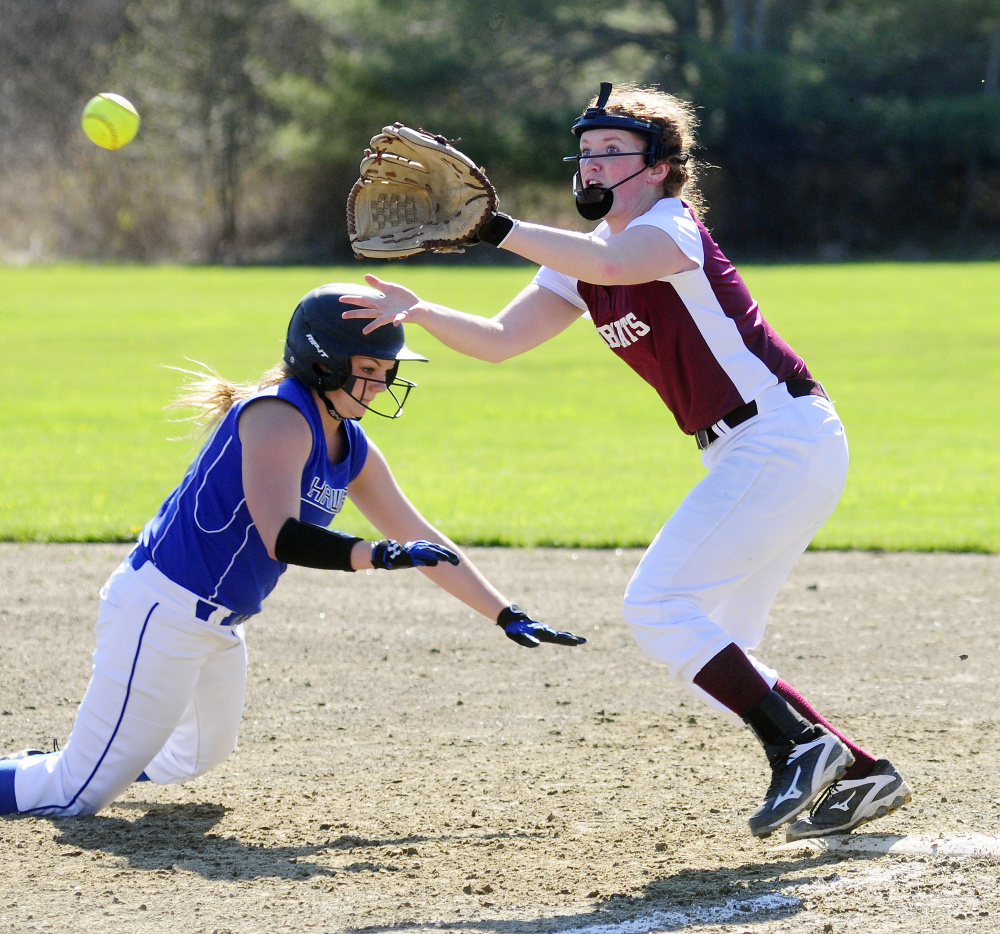Sacopee's McKenzie Fox, left, dives back to first as Richmond first baseman Kelsea Anair waits for the throw Friday in Richmond.