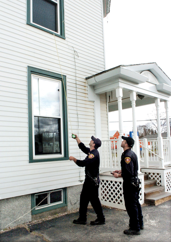Skowhegan Fire Capt. Jason Frost, left, measures the distance from a second story window to the ground as firefighter Scott Libby records the information during a safety inspection Wednesday at an apartment building in Skowhegan.