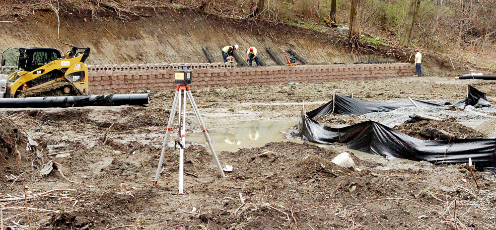 Workers with Ranger Contracting Inc. work on a retaining wall in the rear of a lot at 50 Bay St. in Winslow where a new Dunkin' Donuts is being built. It will replace the one at 9 Bay St.