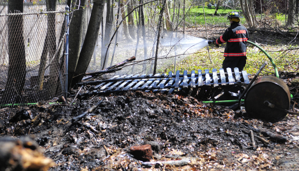 Gardiner firefighter Roy Girard sprays down the area burned by a small brush fire Tuesday behind homes on Pleasant Street in Gardiner.