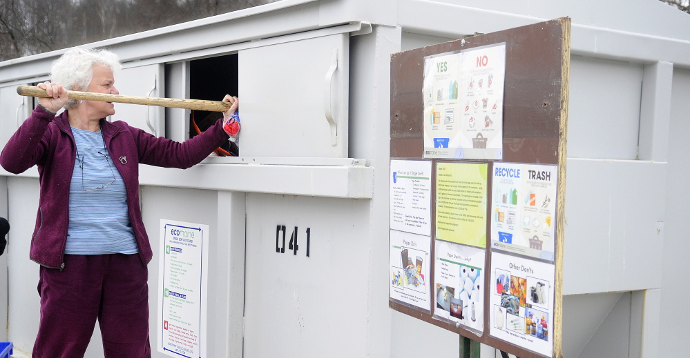 Augusta Public Works Director Lesley Jones tamps down items in the recycling station at Augusta Public Works to make way for other deposits in this April 2, 2015 file photo.