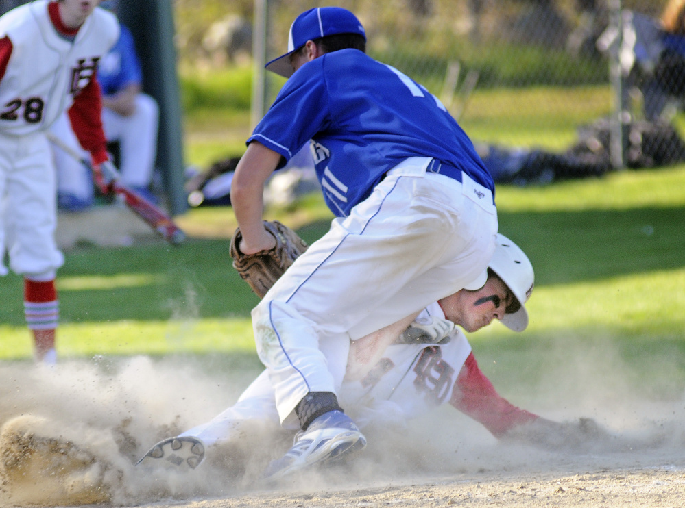 Hall-Dale's Austin Stebbins slides home under Madison's Chase Malloy during a game Wednesday in Farmingdale.