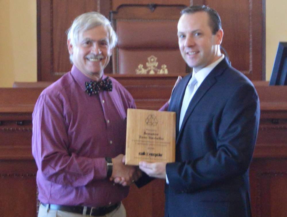 Sen. Tom Saviello, R-Wilton, recieves the Sustainabilty Award from a representative of Call2Recycle for his efforts to remove consumer batteries from the waste stream.