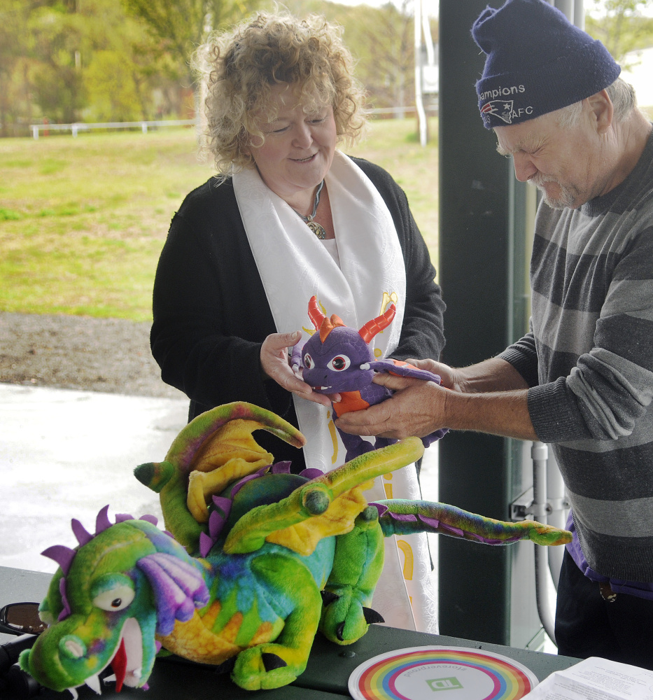 Rev. Carrie Johnsen blesses stuffed dragons belonging to George Stanley, of Greene, during a Unitarian Universalist Community Church service in Augusta Sunday.