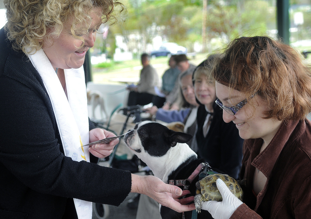 Rev. Carrie Johnsen blesses a dog, Flora, and tortoise, Gigi, belonging to Emma Chapin, of Winthrop, during a Unitarian Universalist Community Church service in Augusta Sunday.
