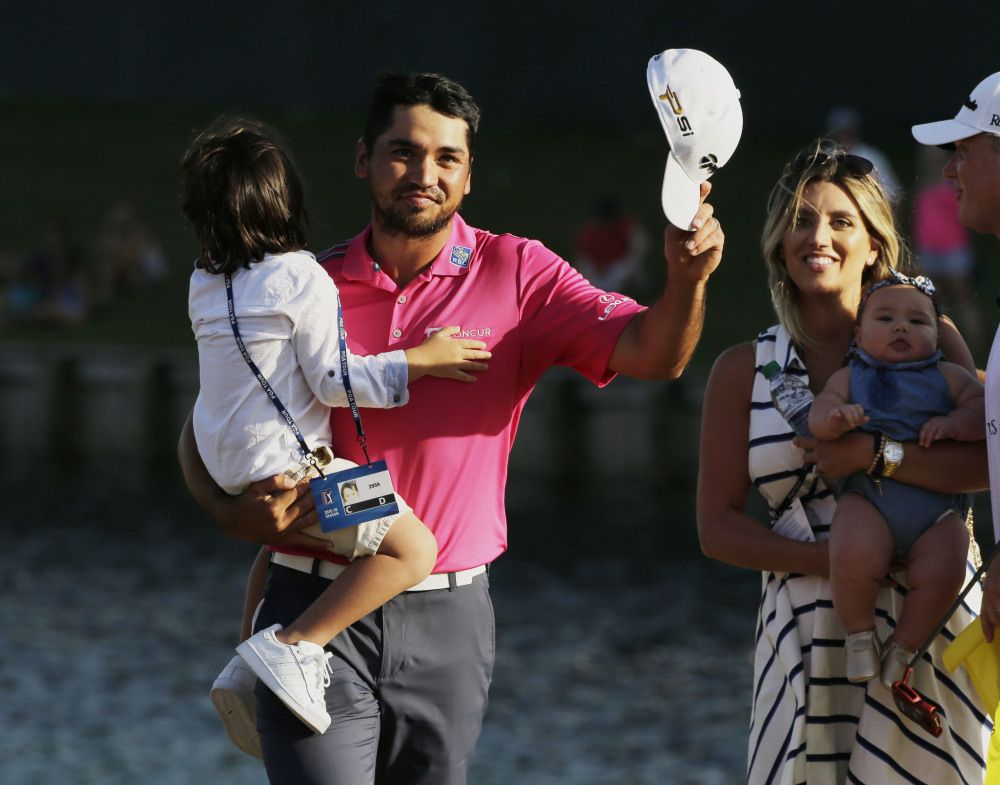 Jason Day tips his hat as he walks off the 18th green with his family after winning The Players Championship on Sunday in Ponte Vedra Beach, Florida. Day is holding his son Dash as his wife Ellie holds daughter Lucy.
