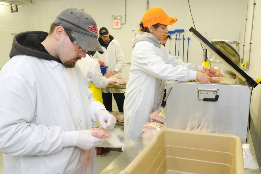 Plant manager Charlie Ripley III, left, packs chicken into bags as co-owner/manager Gina Simmons loads bags into a vacuum sealer in this March 5, 2015, file photo taken at Common Wealth Poultry Co. in Gardiner.