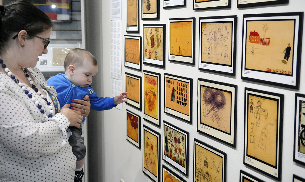 "Danna Hayes and her son, Eli, seven months old, examine art on Monday that was created by children during the Holocaust at the exhibit ""Those People ... Well, They're Not People at All: Children's Reactions to the Holocaust,"" displayed in the Holocaust and Human Rights Center of Maine in Augusta. The elder Hayes, of Bath, is the granddaughter of Holocaust survivors."