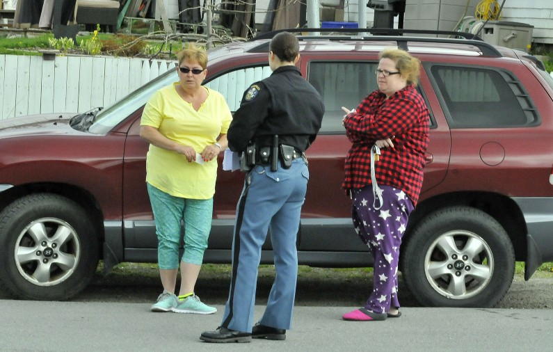 Rebecca Smith, left, of St. Albans, is interviewed by Trooper Jillian Monahan beside her car, where a masked man stole her purse Tuesday in the parking lot of the St. Albans Mini Mart. At right is Smith's friend Kelly Anderson.