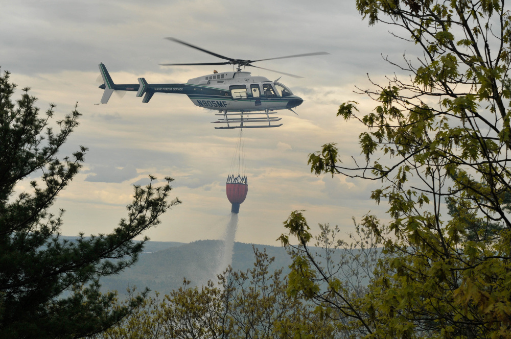 A Maine Forest Service helicopter drops water onto a forest fire Thursday afternoon on French Mountain in Rome.