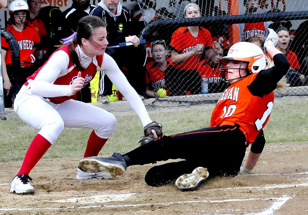 Staff photo by David Leaming   Skowhegan's Eliza Bedard slides safely into home plate as Messalonskee pitcher Kirsten Pelletier, left, covers.