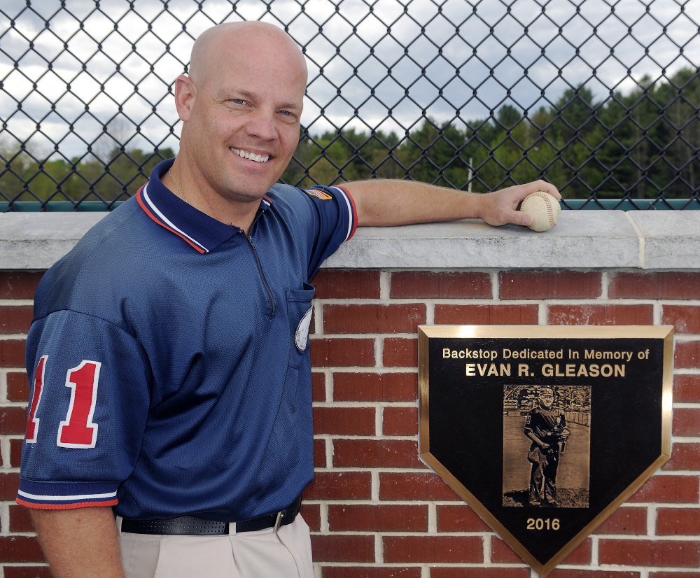 Keith Gleason stands next to the plaque in memory of his father, umpire Evan Gleason, beneath the new backstop at McGuire Field on Thursday in Augusta.
