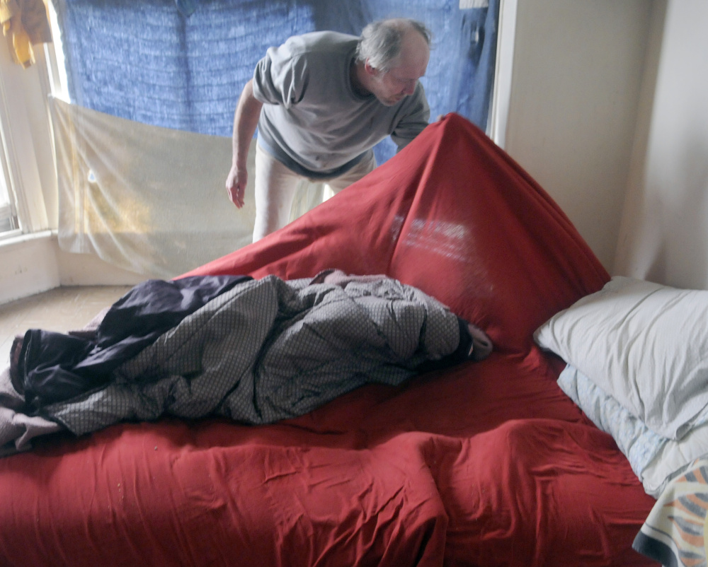Al Sugden searches his bedding for bedbugs May 3 in his room at 382 Water St. in Augusta. City officials said last week that work to eradicate bedbugs continues in that building.