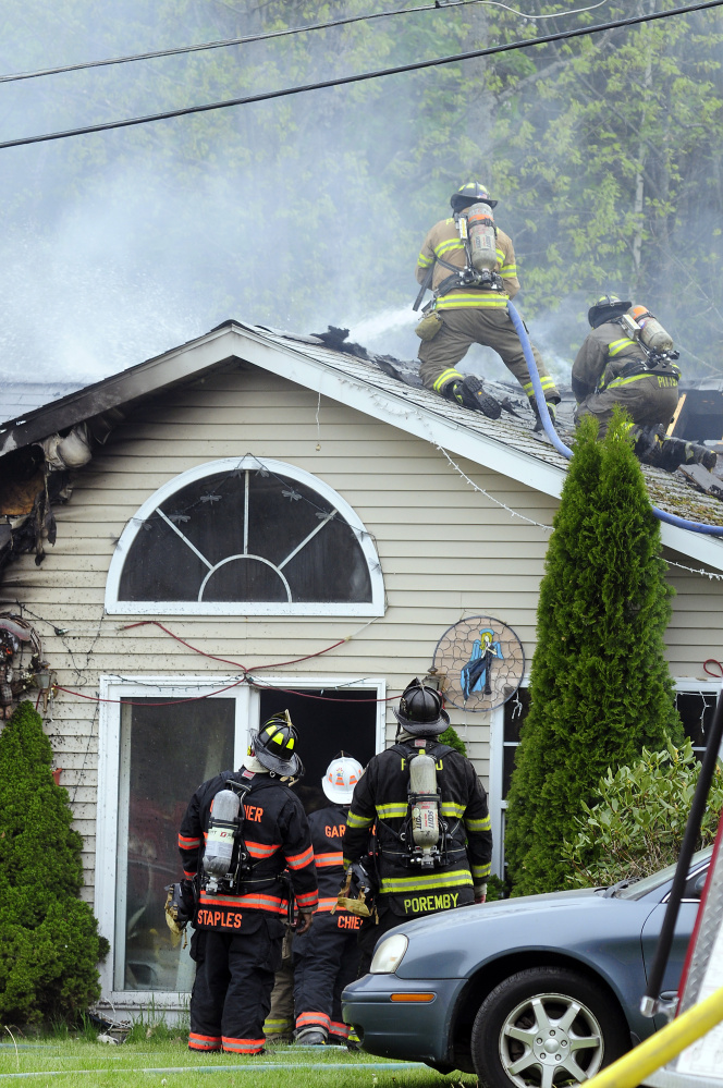 Firefighters work on the roof Saturday to put out a house fire on Pushard Lane in Gardiner.