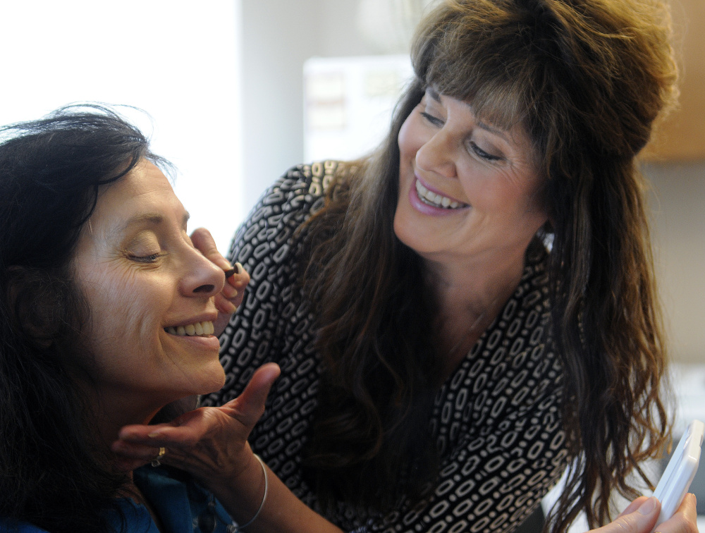 Victoria Littlefield, right, teaches Kenlyn Clark, of Waterville, how to apply makeup on Monday at the Alfond Center for Cancer Care in Augusta. The Pittston salon owner is being honored for her volunteer work helping women feel better while undergoing cancer treatments.