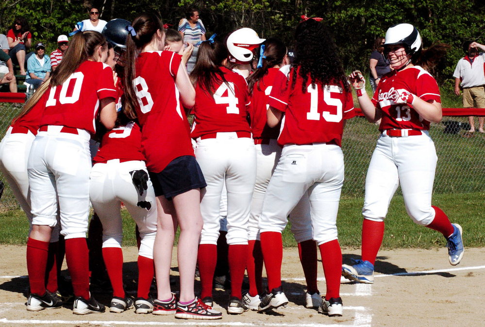Messalonskee's Hannah Duperry is welcomed at home plate by a large greeting party after she belted a home run against Cony during a Kennebec Valley Athletic Conference Class A game Monday in Oakland.