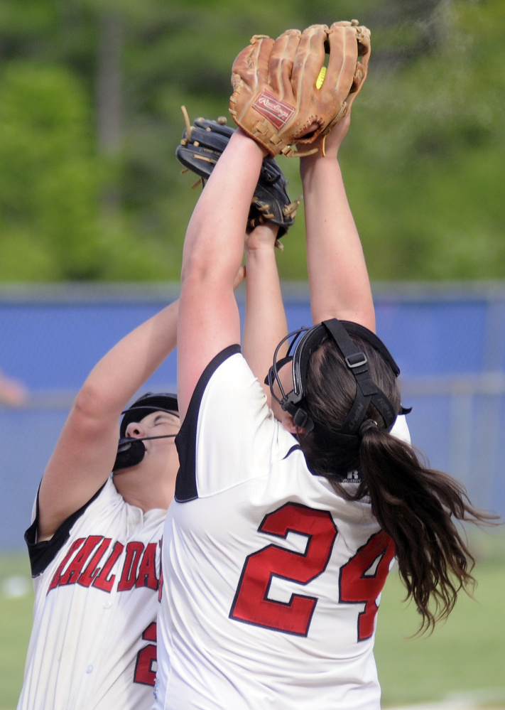 Hall-Dale's Becca Ackerson, left, and Hailey Taker collide while going for a pop up on the mound during a game against Oak Hill on Monday in Wales.