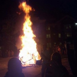 Firefighters respond to the scene of a bonfire at Colby College on Sunday. The department and Waterville police said the crowd was aggressive, and one student was arrested on charges of assault and refusing to submit to arrest.