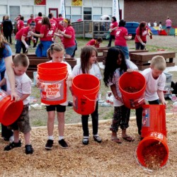 North Elementary School kindergarten students made a bucket brigade and dumped wood chips on playground at the Skowhegan school during the New Balance Skowhegan employees volunteer event on Wednesday. The event was part of NB SparkStart Global Volunteer Week.