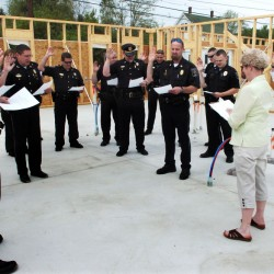 Oakland Town Clerk Jan Porter swears in Oakland police officers and Town Manager Gary Bowman, at right, inside the construction zone of the new department building on Wednesday.