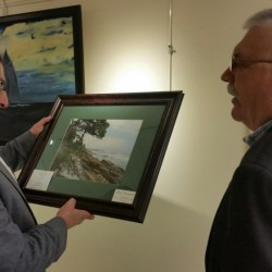 Gov. Paul LaPage accepts a photograph of the Maine coast Thursday from Alan Foley, right, the photographer, at Inland Hospital's Healing Art Gallery. LePage visited the Waterville hospital's gallery, which is displaying art by veterans until Tuesday.