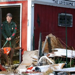 Maine Warden Service Sgt. Roger Guay and one of his two dogs search a shed in Randolph in 2004. Guay, who retired after 25 years with the Maine Warden Service, has been involved in more searches for missing people than he can count. He said hikers have to be prepared, both to stay alive and to help searches find them.