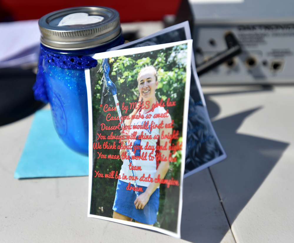 A picture of Cassidy Charette is tied to jar of sand representing dreams at Thomas College in Waterville on Thursday.