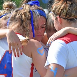 Messalonskee High School senior lacrosse players embrace during a moment of silence in memory of Cassidy Charette at Thomas College in Waterville on Thursday.
