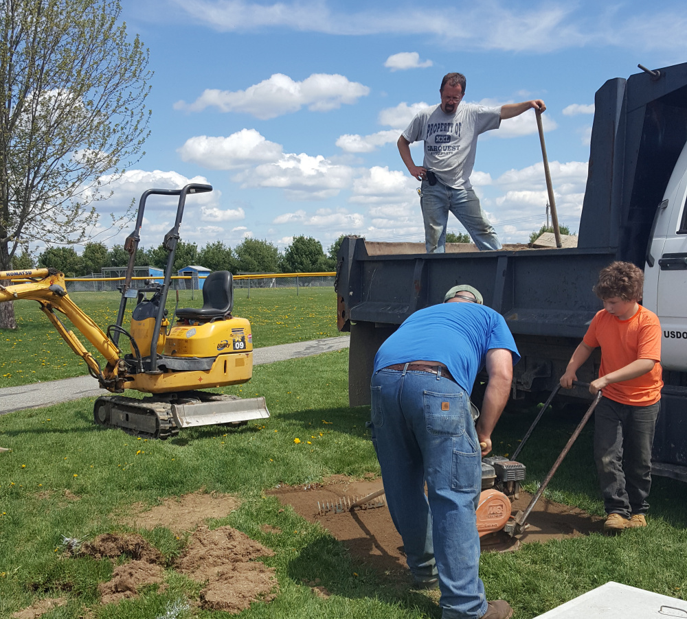 Volunteers Greg Parker, in truck, Liam Poulin and Jason Dumais, back to the camera, help install buddy benches at Benton Elementary School. Liam's father, Len Poulin, who owns a construction and excavation business, volunteered to install the benches, bought with money raised by the Student Council.