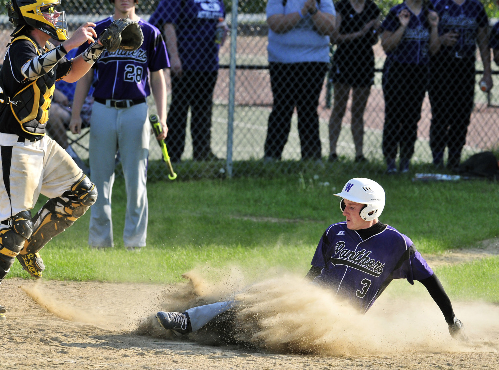 Maranacook catcher Mark Buzzell waits for the throw as Waterville runner Justin Wentworth scores to give his team a 3-1 lead in the seventh inning Friday.