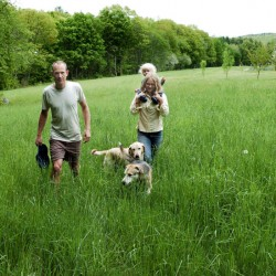 Marc and Lyra Collard, daughter Ara and dogs walk in a field Tuesday in Norridgework, where they are establishing the Winding Hill Trails. The couple are opening the free public-access walking and running trails on their property with help from a New Balance Move More Kids grant.