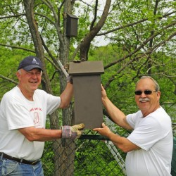 City Councilor Pat Paradis, left, poses with Ray Fecteau and a bat house Friday at the Mill Park pétanque courts in Augusta. Fecteau said he hopes the bats might eat bugs attracted to the lights at the court during evening play there.