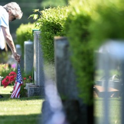 Mary Alice Rancourt places a flag at the gravesite of her late husband Saturday at St. Francis Cemetery in Waterville.