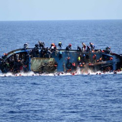 People try to jump in the water right before their boat overturns off the Libyan coast on May 25. Over 700 migrants are feared dead in three Mediterranean Sea shipwrecks south of Italy in the last few days as they tried desperately to reach Europe in unseaworthy smuggling boats, the U.N. refugee agency said Sunday.