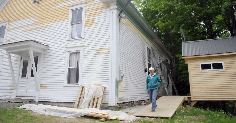 Marianne Archard walks down the new ramp at the Vienna Union Hall on Sunday. Renovations to the public performance space are underway, including a new outhouse, at right.