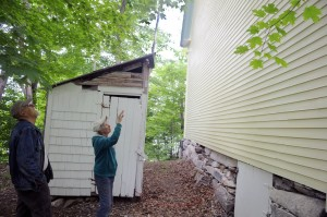 Marianne and John Archard examine the exterior paint on the rear of the Vienna Union Hall on Sunday. Renovations to the public performance space are underway, including a replacement of the outhouse at left.