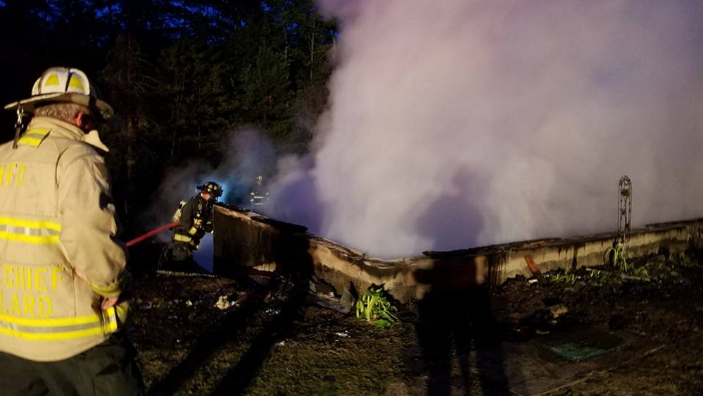 Firefighters douse embers in a basement at 141 Tillson Road in Monmouth. A two-story, single-family home there was destroyed in an early morning blaze Monday. No one was home at the time and no one was injured, according to Monmouth Fire Chief Dan Roy Jr.